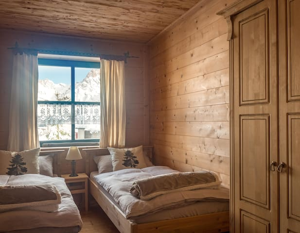Wood paneled second bedroom with two twin beds.