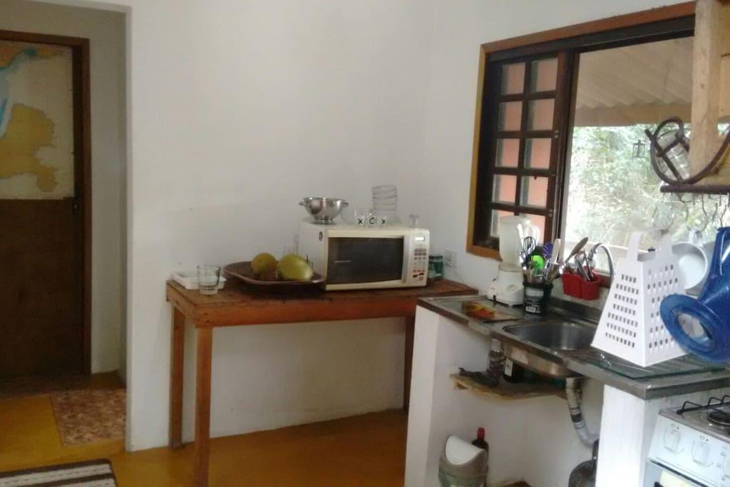 A nossa cozinha vista da porta de entrada, a porta fechada com uma carta náutica decorando é a porta do quarto!