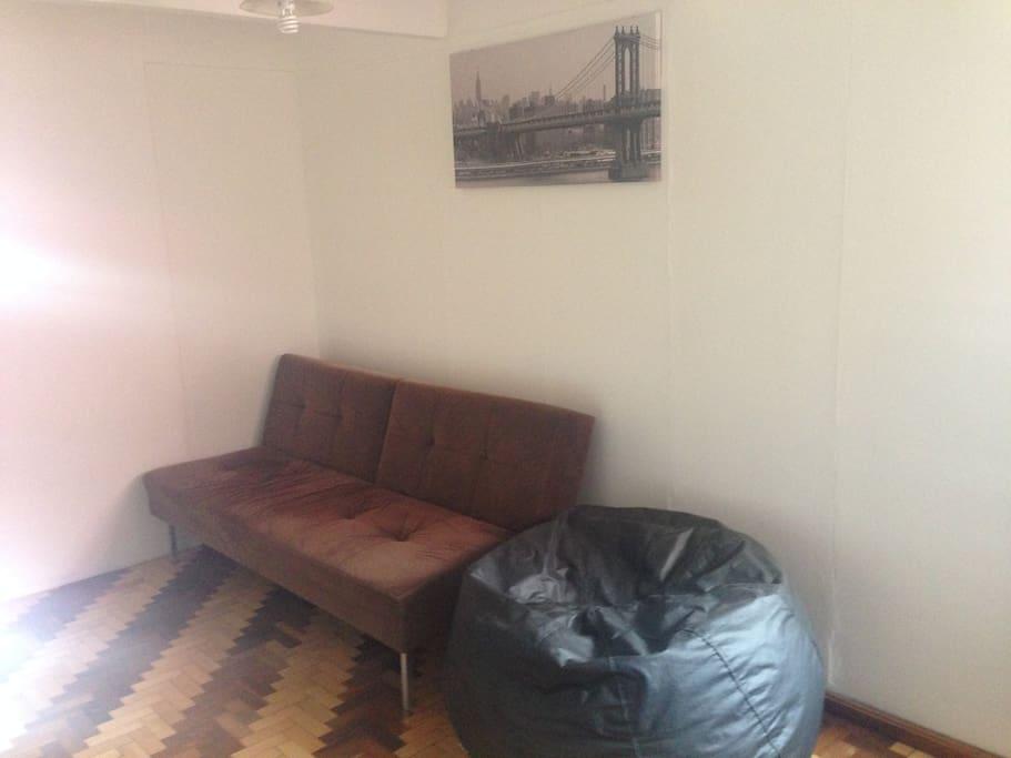 Sofá-cama casal e Puff em frente a TV