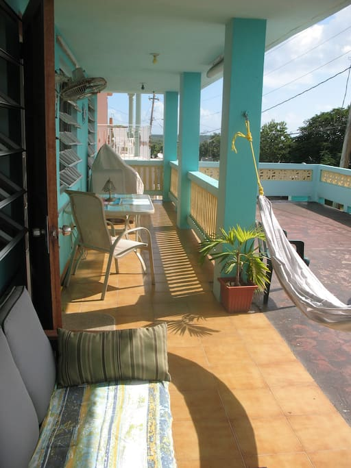 Sunny balcony shows the entrance to the room. table and chairs, hammock.