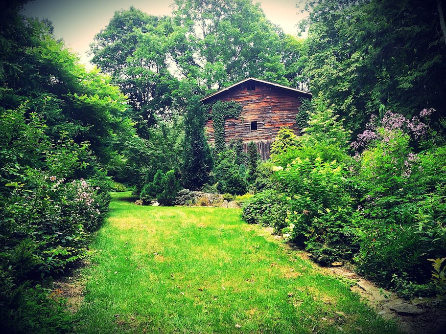 Old tobacco barn with professionally-designed woodland gardens on 12 acres, featured in Southern Living magazine in 2011, with cascading stream, walking paths, sitting areas, hammock, fire pit and more.