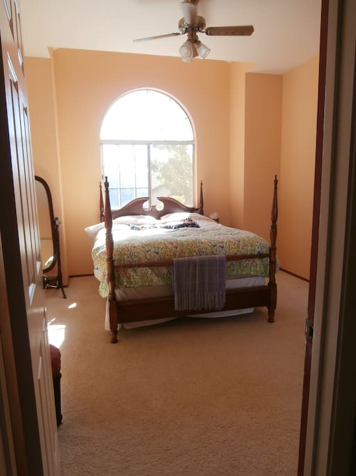 This is spacious bedroom filled with sunlight.