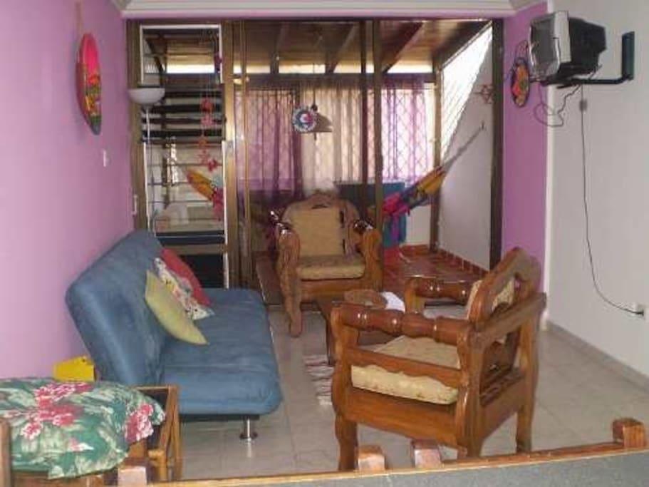 Aquí se ve la sala donde está el televisor y donde está un sofá cama doblé. Los sillones son de madera noble de Samán.