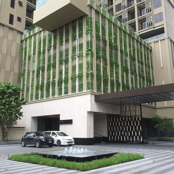 Building decorated with vertical garden and fountain at main entrance to welcome residences.