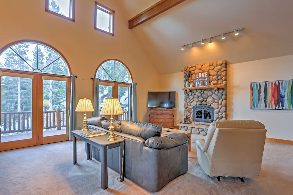 Cathedral ceilings, beautiful arched windows,  and a stone wood-burning fireplace create a warm and inviting environment.