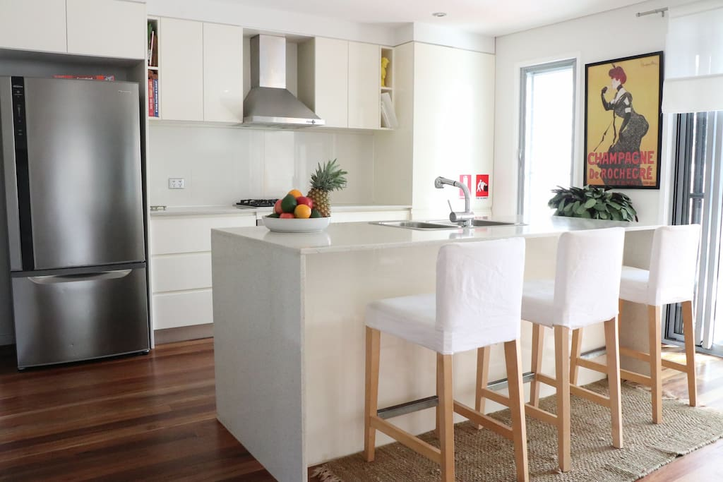 Modern kitchen with xl fridge, double dishwasher, oven, kettle, toaster, microwave and caesar stone bar