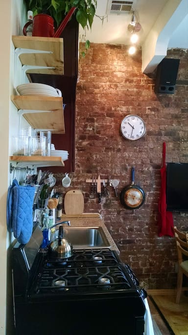 We love our hand-made kitchen shelves and, of course, the brick wall.