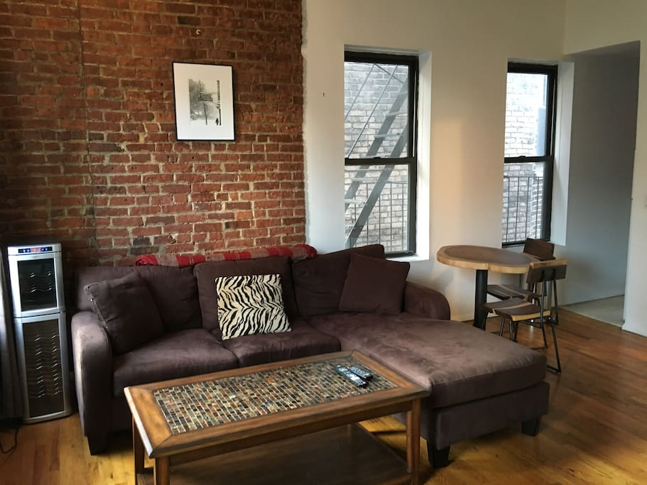Main room with exposed brick, high ceilings and cedar beam accents. The perfect place to relax and enjoy some down-time after an exciting day in the city. Working wine fridge. Surrounded by windows and light. Couch can comfortably sleep 1+