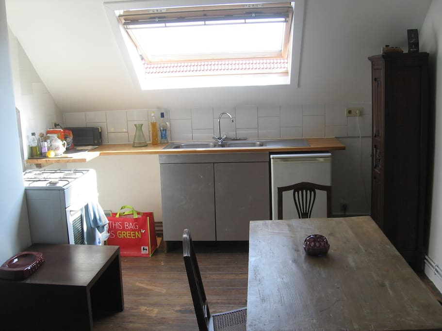 Kitchen - dining room ( gas cooker , fridge, crockery, kitchen utensils) , a table and three chairs, a chest of drawers.