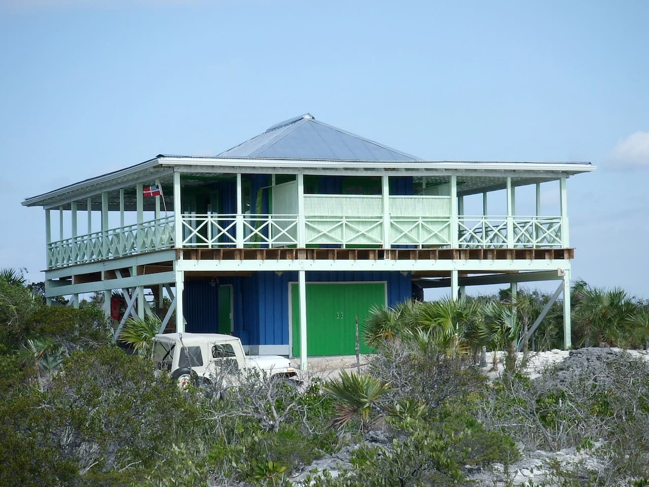 The Boathouse with 235 feet of white sand beach and a beach tiki hut with chaise lounges