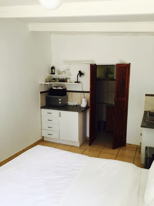 Kitchenette with coffee station and essential appliances. En suite bathroom with shower.