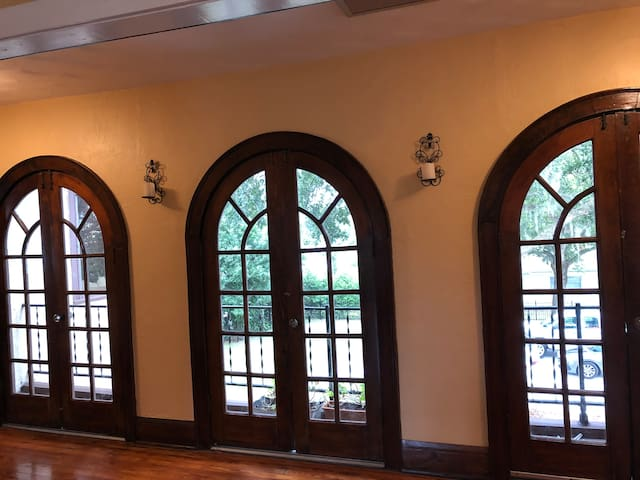 Original wood arched doorways leading out to the back balcony