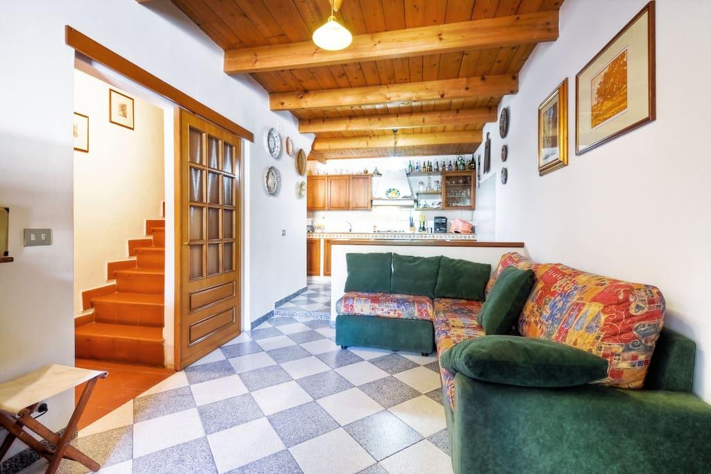Zona giorno, posta al primo piano, con angolo cottura e divano letto matrimoniale. Le scale portano al secondo piano e al piano terra dove è presente il portone di ingresso.