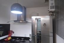 Cozinha com aquecedor à gás. Geladeira, cooktop à gás, coifa