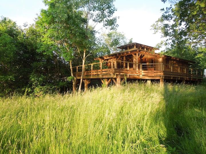 Cabane de charme tout confort, terrasse sur étang