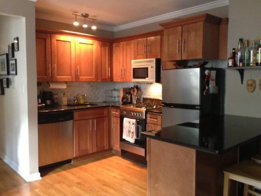 Open kitchen with gas stove, microwave, dishwasher. toaster, coffee maker, blender, the works.