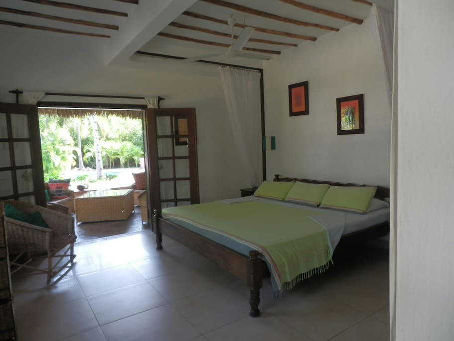 Master bedroom with ensuite.  Doors open to patio and view of pool and garden.