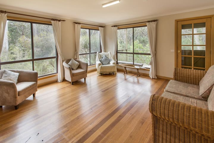 The second living area downstairs, with stunning views over the tranquil bushland and wildlife - opening up to private deck outdoor entrance.