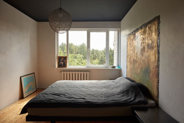 Bedroom is seperated from the living room, but it still has the same forest view.