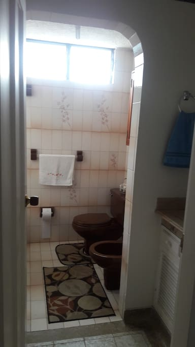 Baño con sanitario, lavamanos y tina-ducha