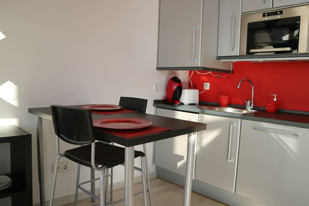 Cocina con zona de desayuno con mesa alta.