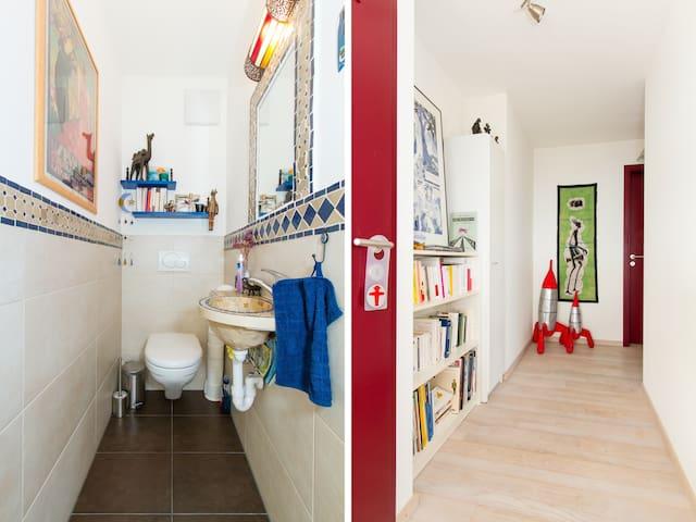 Toilettes et couloir qui mène aux chambres à coucher et salle de bain