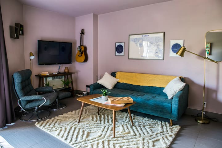 """Living """"room"""" area. TV can be angled to watch from bed! Couch folds out into a bed, sheets provided for it. Vintage style reading chair and ottoman. Guitar, games, Sonos speaker. Air Conditioning/Heat unit (fan and extra heater available)"""