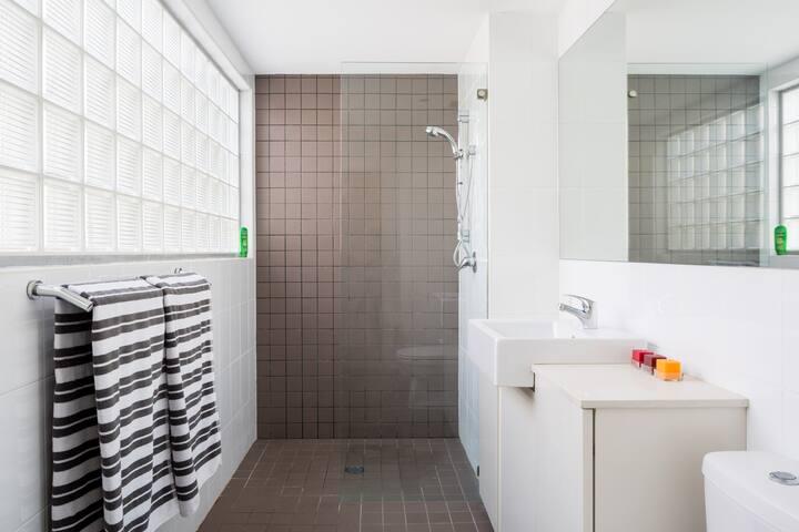 Modern, light bathroom with power shower.