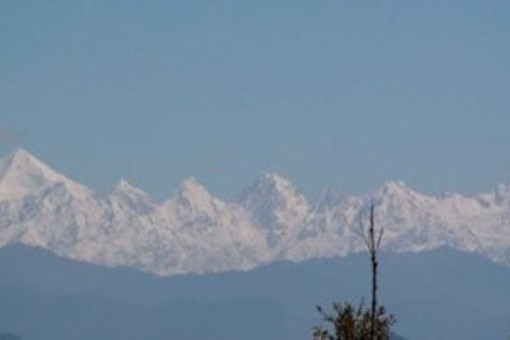 Himalayan snow peaks view from House garden and sitting area inside .