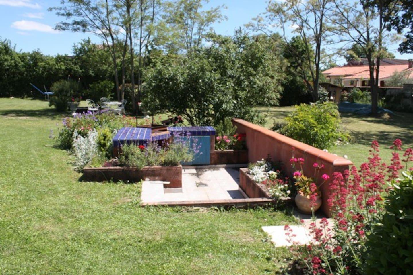 jardin fleuri avec barbecue et salon de jardin