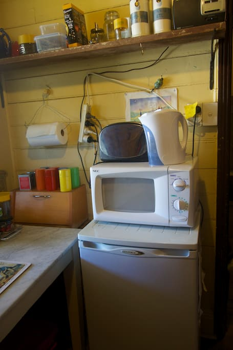 Kitchen: small fridge, microwave and old-timey marble workbench.