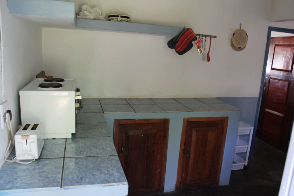 Kitchen, with electric counter stove, gas plates, fridge and freezer.