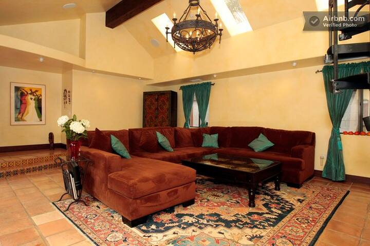 Large comfy living room with large TV surround sound, and cathedral ceiling