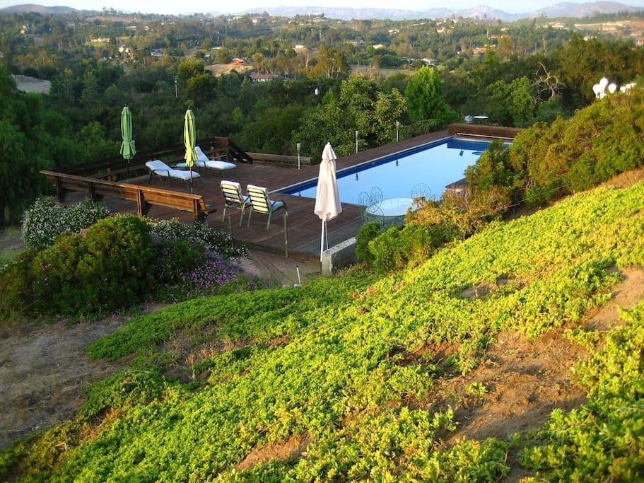 Backyard pool, redwood deck, dining table, & views.
