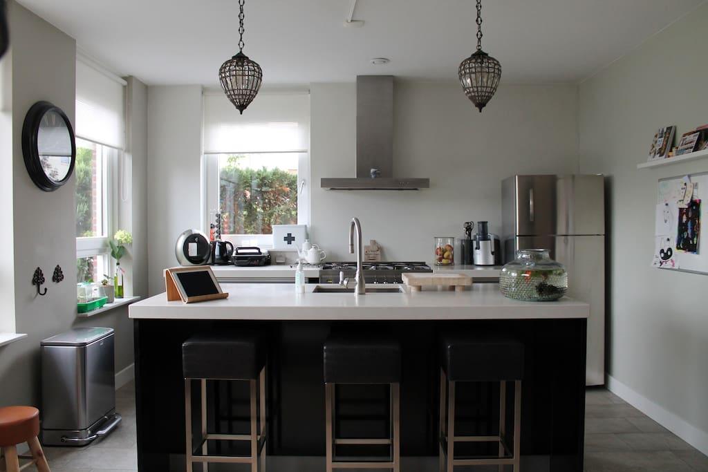 Compleet uitgeruste keuken met luxe fornuis, magnetron en vaatwasser.