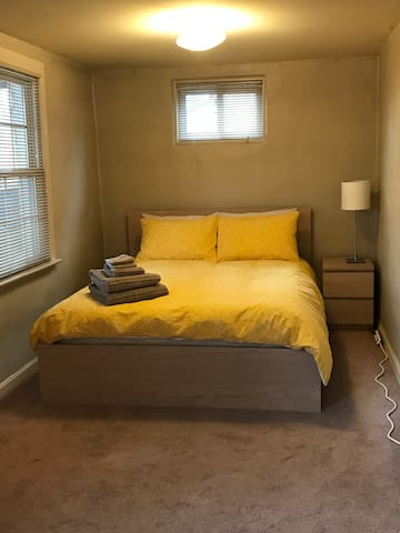 Queen bed with IKEA memory foam topper; duck/goose down comforter; towels provided. Room has two overhead light fixtures, 2 table lamps, and 3 windows.