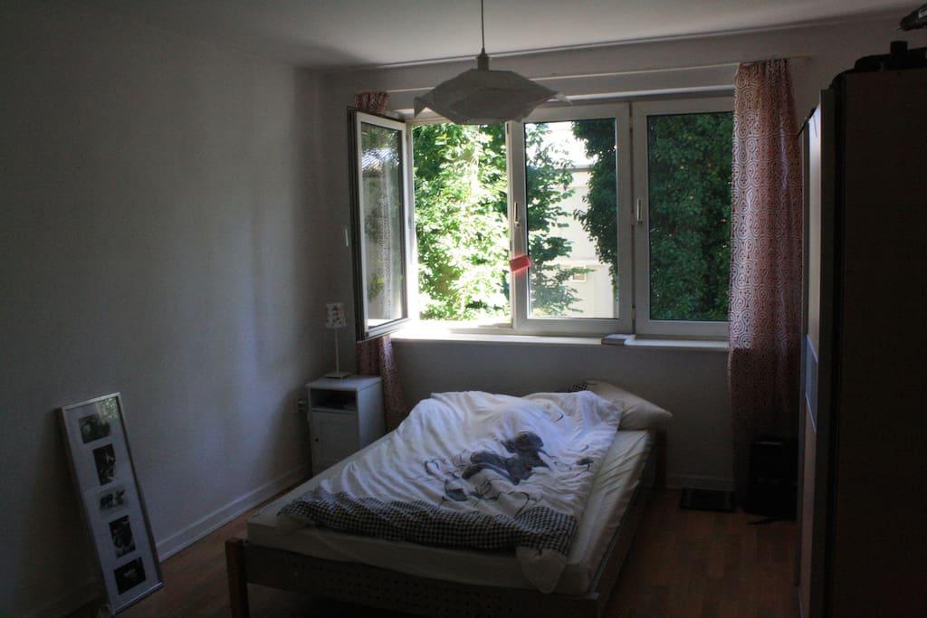 Schlafzimmer mit Doppelbett zum Garten raus