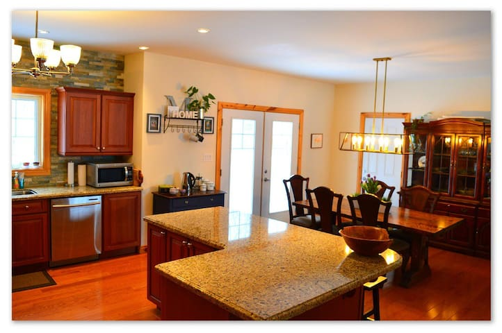 Open concept kitchen overlooking forest, with large island opening on to dining room