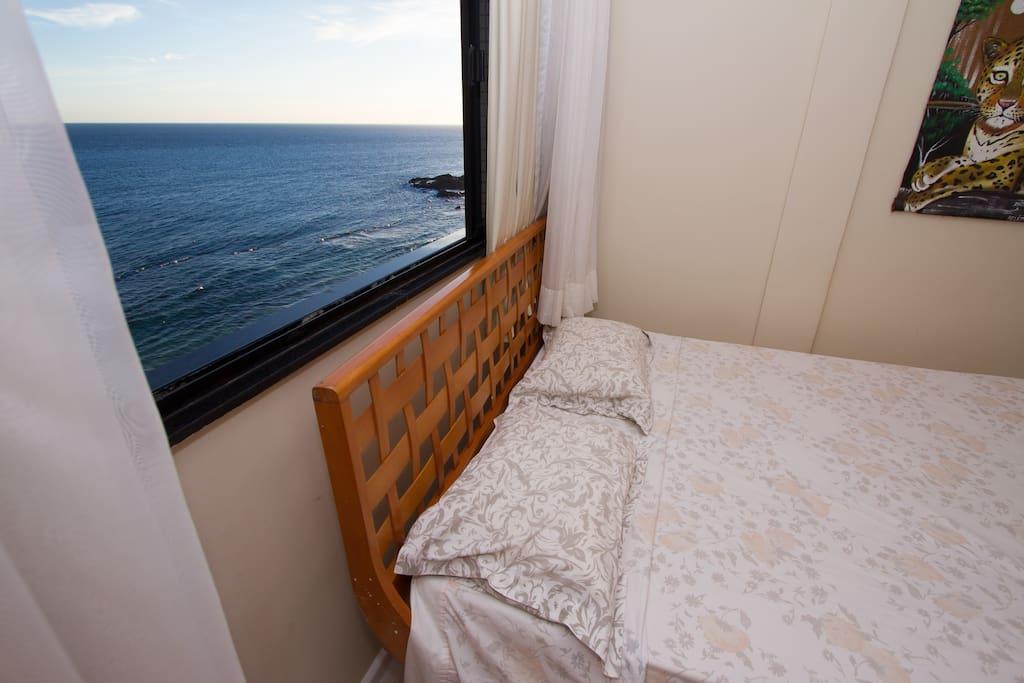 Quarto com cama de casal e vista mar.