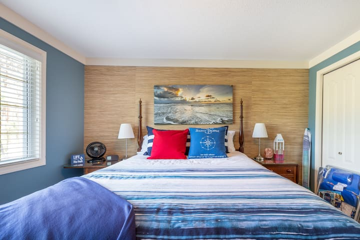 The blue bedroom is on the ground floor and has premium linens and a lake view. It has its own full bathroom with custom walk-in shower in the hall.