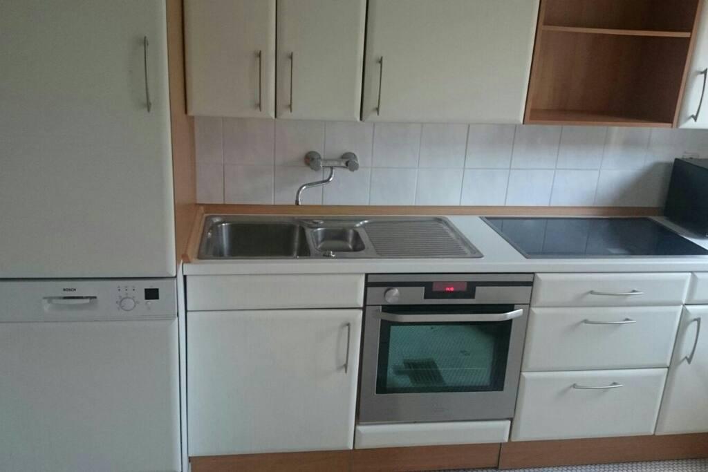 Küche mit Spülmaschine, Induktionskochfeld, Mikrowelle und Kaffeevollautomaten. Im Kühlschrank befinden sich Getränke zu kleinen Preisen