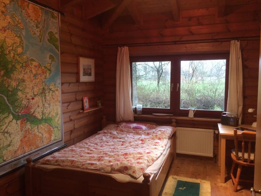 Schlafzimmer mit Bett, Arbeitsplatz und Schrank
