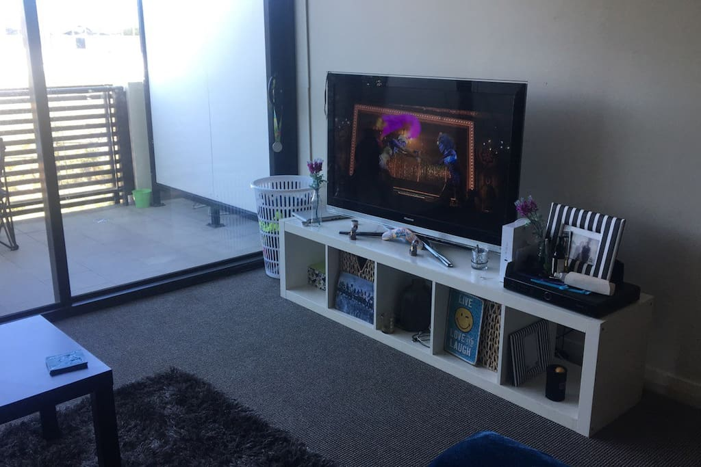 Large living area with massive tv, wifi, L shaped couch