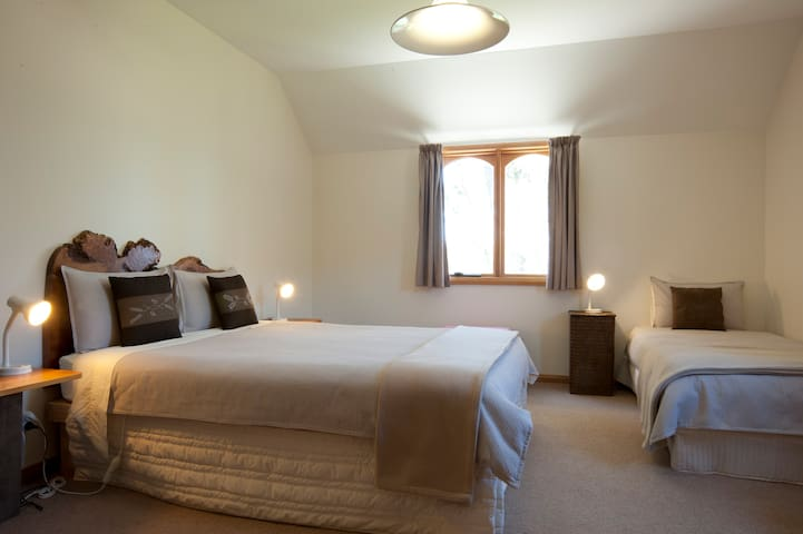 Spacious main bedroom with queen and single beds