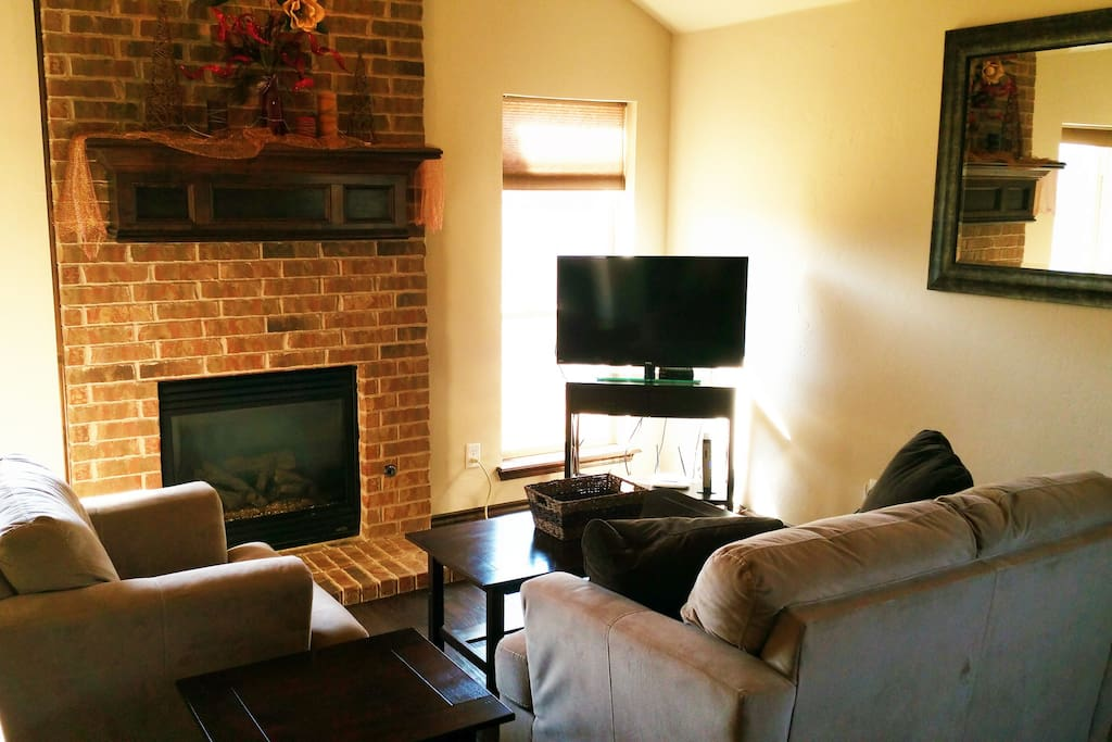 Gas fireplace and hand-scraped wood floors in den