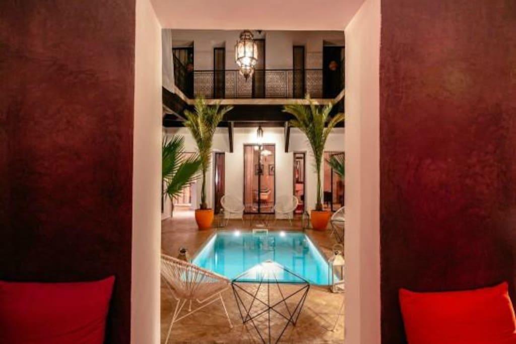 Vue du patio depuis le salon d'été, ouvert sur la patio et sa piscine