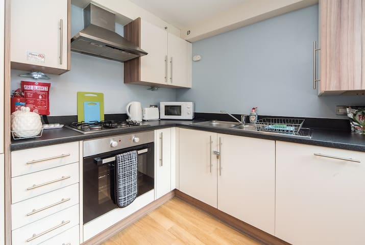 The kitchen area with cooker, gas hob, fridge-freezer, dishwasher, extractor fan and microwave. Tea, coffee and sugar are provided.