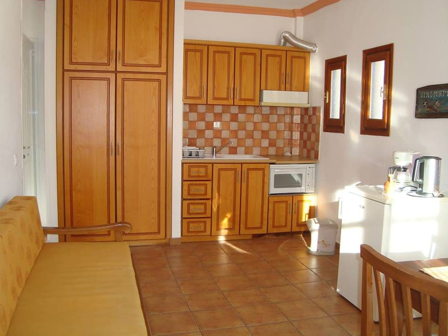 Kitchen with living room and 2 balconies with view to garden and village Kokkari.