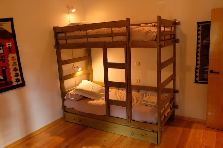 Habitación infantil con litera y cama individual supletoria