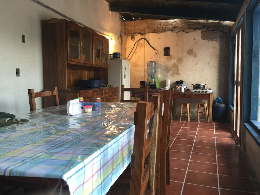 Full kitchen with wood and gas stove, fridge, dishes and utensils.
